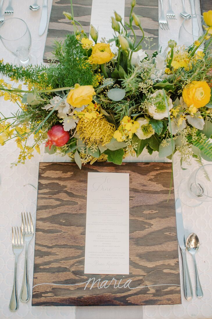 Instead of place cards, the couple had each guest's name hand painted on a square wooden charger placed at each place setting.