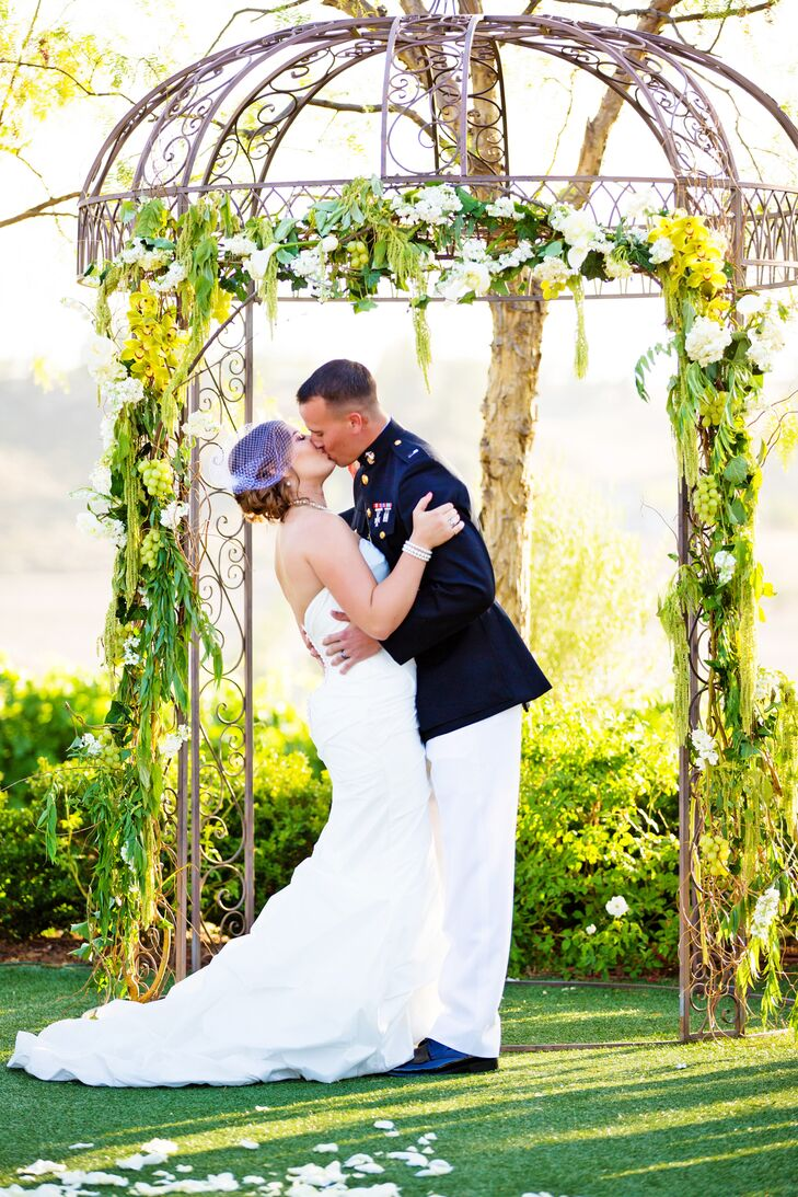 Newlywed's First Kiss Under an Arch Entwined with Vines