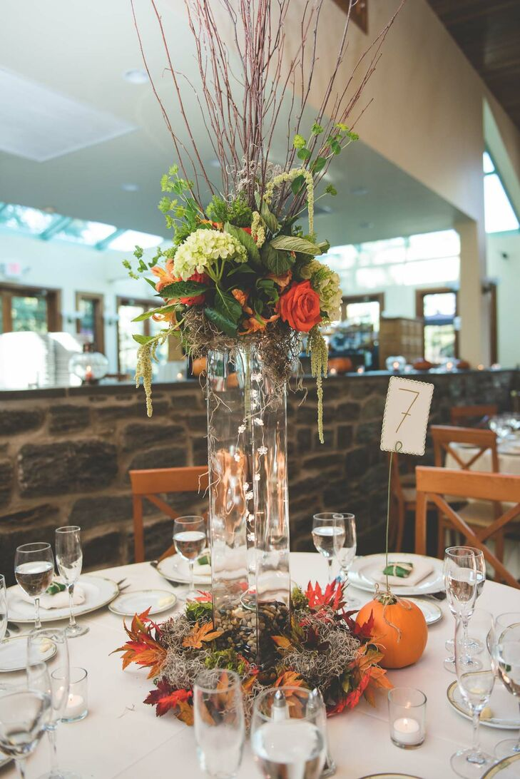 """We wanted our centerpieces to look sort of like an autumn forest, partially inspired by 'Lord of the Rings,' "" Katie says. ""Justus actually designed the base of the centerpieces, and the florist completed the look with her arrangement that sat on top of the vases."""