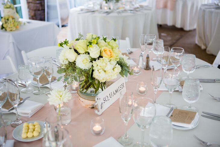 Guests found their seats at dining tables marked with signs, inspired by places along the Hood Canal. White and peach floral centerpieces accented the middle of dining tables, surrounded by votive candles on top of champagne runners.