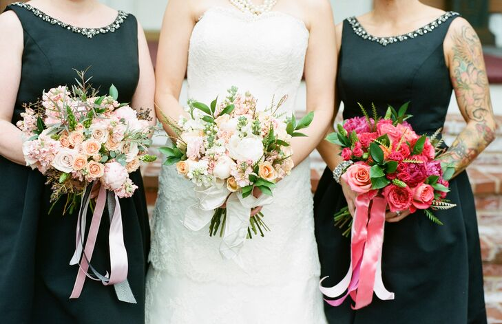 Jo and her bridesmaids carried bouquets of roses, peonies, stock and greenery in different colors. Jo's bouquet was ivory with blush accents, held together with ivory ribbon. One of her bridesmaids carried a blush bouquet tied with blush ribbon while the other carried a deep pink bouquet with a pink ribbon.