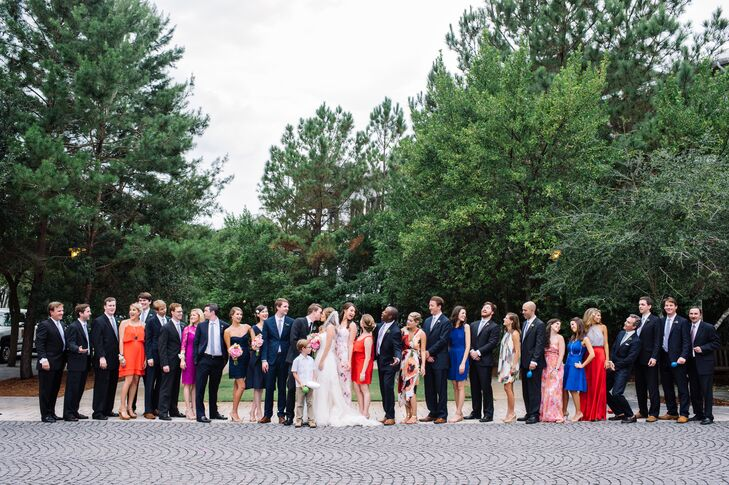 Caroline and Christopher's wedding party included almost every color. All the groomsmen, including his best man, wore navy suits with white shirts and gingham ties, creating a uniform look. Their bridesmaids, however, donned dresses in all their favorite colors, prints and styles. Caroline's two sisters stood out from the pack with navy blue dresses and pink bouquets. The rest of the women wore flowers in their hair.