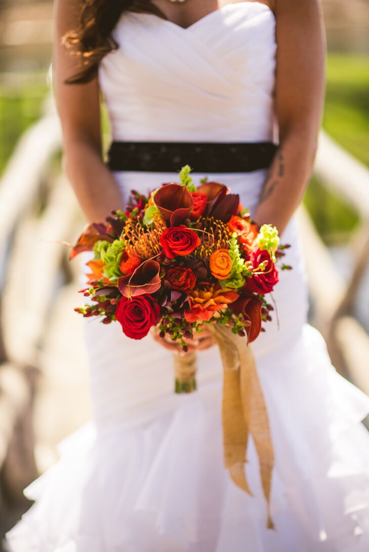 Their favorite flower, the mango calla lily, popped up in arrangements throughout the wedding, including Ashley's bouquet. She worked with Ibranyi Is Floral to fill it with earth-tone-inspired flowers. Red orange and crimson roses, orange and red ranunculus, orange dahlias, red hypericum berries, orange proteas, greenery and, of course, their calla lilies were all put in the bouquet and wrapped in burlap.