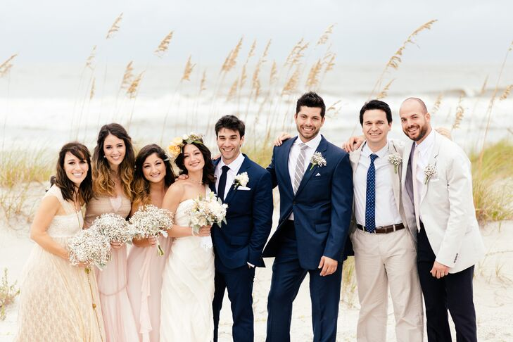 Noelle and Patrick gave their bridesmaids and groomsmen free reign over their wedding day attire. The girls donned long flowing gowns in shades of blush and champagne and carried bundles of fresh baby's breath down the aisle, while the groomsmen wore their own neutral and navy colored suits.