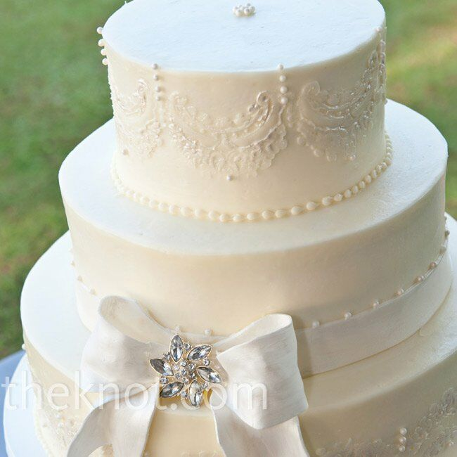 Lace-inspired piping, pearls and crystals decorated the buttercream cake.