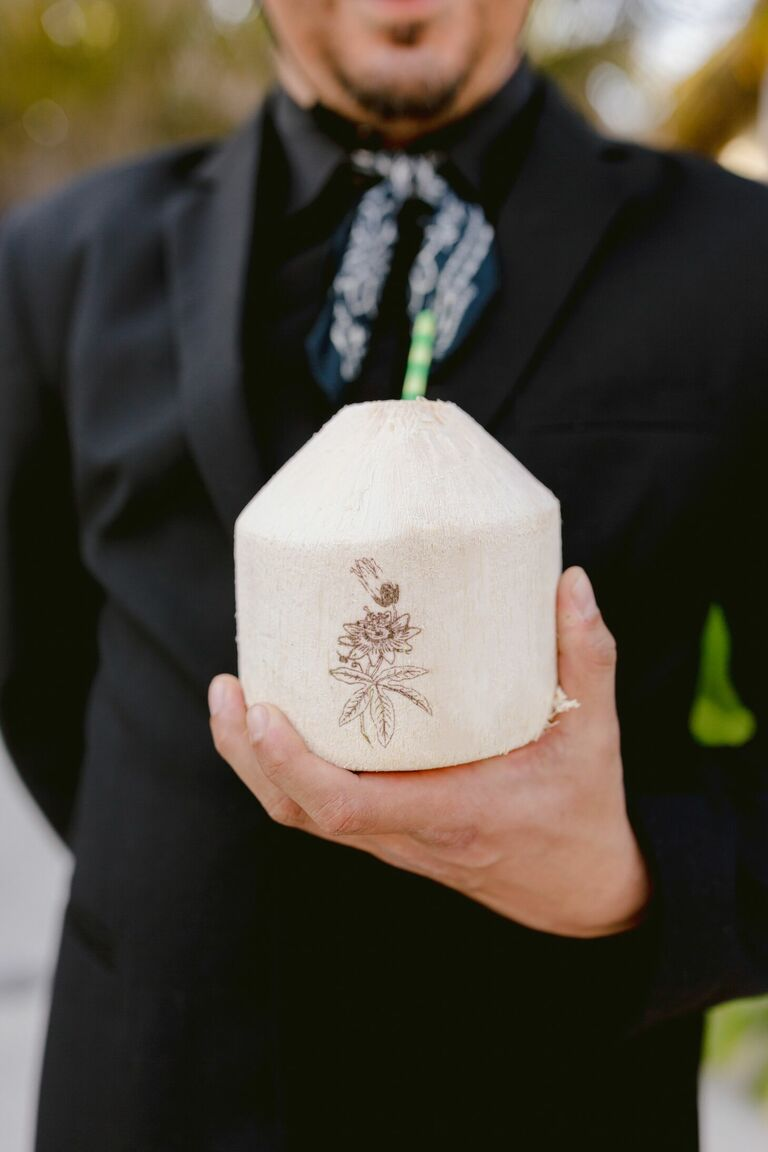 Waiter holding signature cocktail in fresh coconut