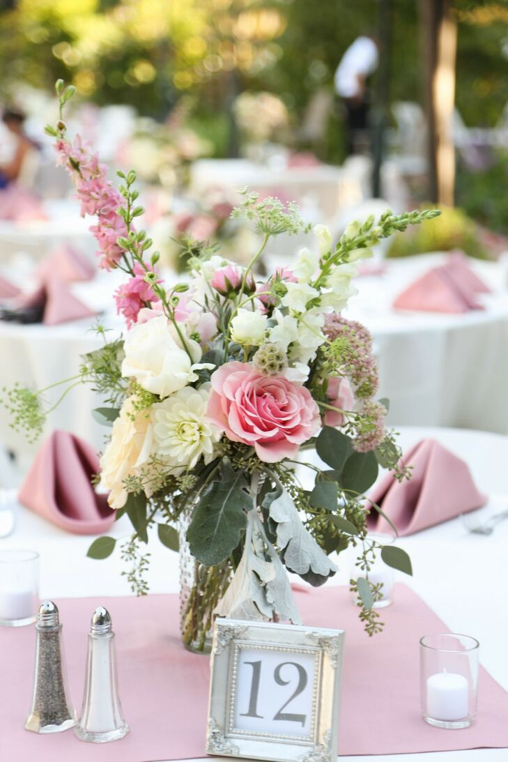 """""""Our florist, Lani Elizabeth, blew us away with their beautiful arrangements and excellentrnflower choices,"""" says Samantha. """"The flowers they used included garden roses, hydrangea, spray roses, Café Au Lait dahlias, pieris japonica, dusty miller, eucalyptus, Queen Anne's Lace,and blushing bride protea. We chose classic white and ivoryrntable linens that allowed the venues naturally beauty and our floral choices to shine.""""rn"""