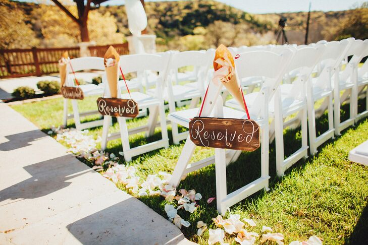 "Leading up to the wooden gazebo ceremony spot were white folding chairs with custom wooden signs inscribed with white calligraphy that said ""reserved."" Blush and ivory rose petals lined the limestone aisle pathway."