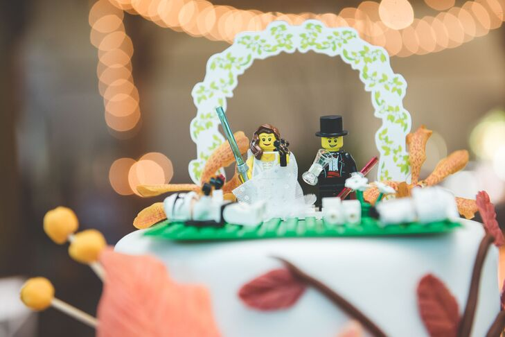 """The couple found a Lego cake topper set, which they modified to have the couple holding light sabers battling droids. """"The little Lego guys throughout the other tiers of the cake were meant to show different things that are part of both our lives,"""" Katie says."""