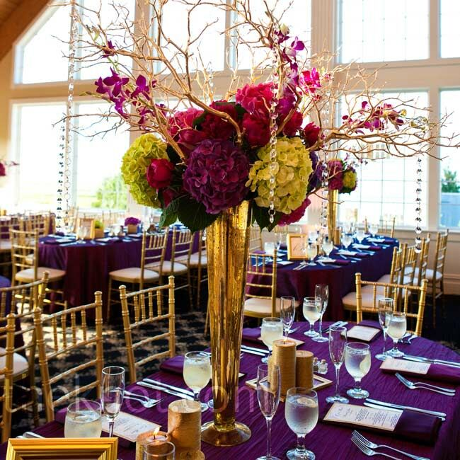 Gold mercury-glass vases and manzanita branches framed full arrangements of bold-hued hydrangeas and peonies.