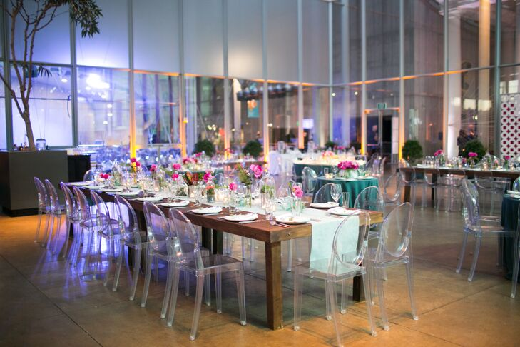 At the California Academy of Sciences reception in San Francisco, long wooden tables are set with pale aqua runners and topped with terrariums and pink flowers.
