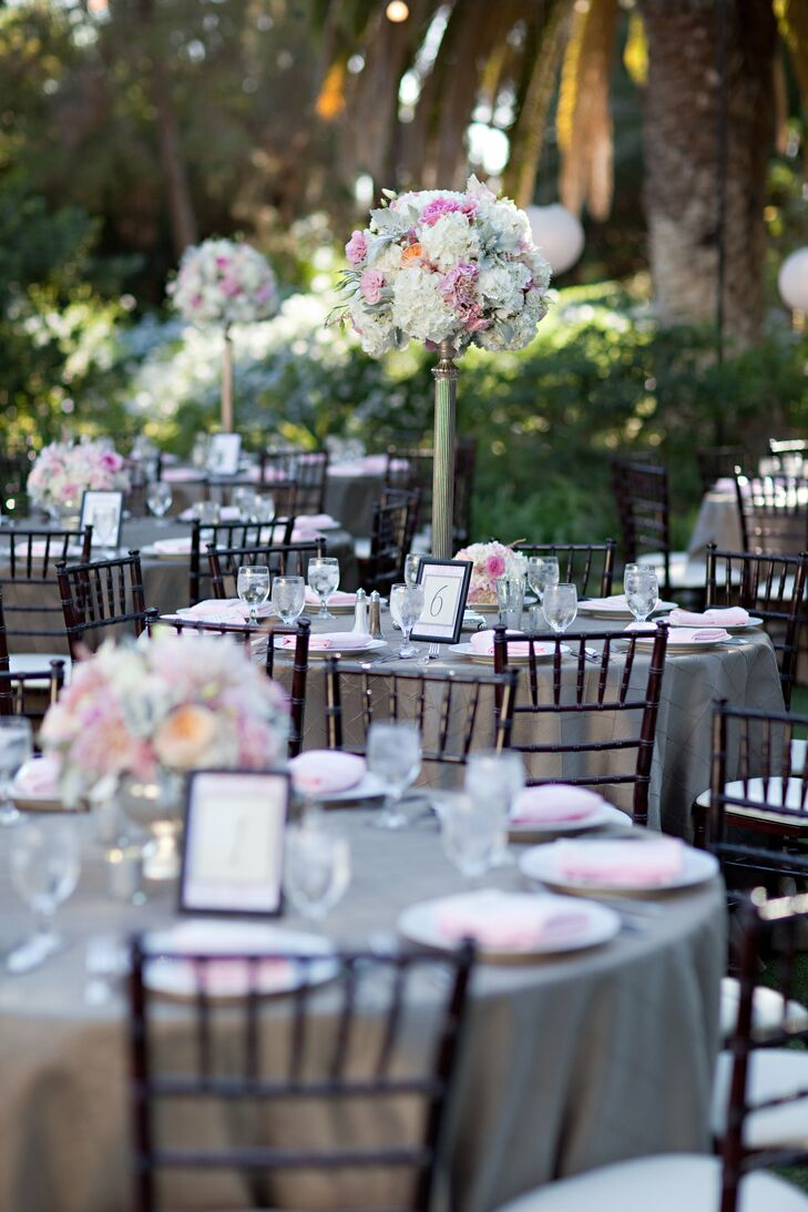 Tall arrangements of pastel hydrangeas and roses were displayed next to lower arrangements at the tables.
