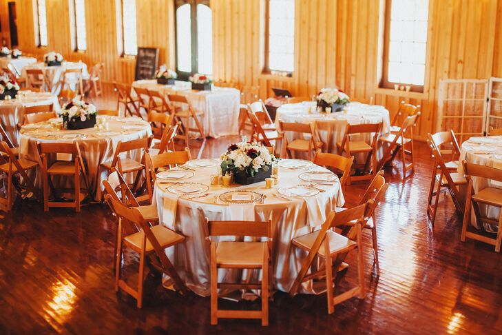 Champagne-colored table linens fit the rustic interior of the Bella Springs Events reception hall, while wooden folding chairs tied in the wooden walls and floors. A combination of round tables and a rectangular head table surrounded the dance floor in the center of the room.