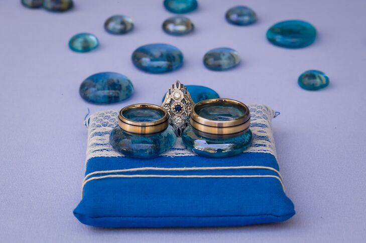 The couple's gold wedding rings that were exchanged at the ceremony were propped up on blue stones supported by the blue-and-white-striped ring pillow. Aly's engagement ring was positioned in the middle, which was silver in a diamond shape accented with a round-cut sapphire in the middle of two round-cut diamonds. The rings were designed by Brilliant Earth.