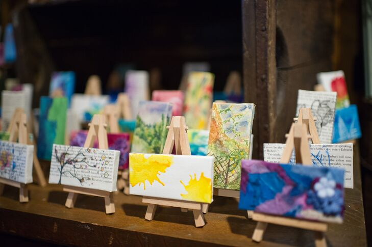 """""""We really wanted our guests to feel special. It was so important to us that each guest truly felt that we wanted them there,"""" says Rachel. """"I spent quite a bit of time painting 200 individual 2x4"""" canvases that sat atop little tiny easels. I wanted each guest have their own piece of art to take home, from my heart to theirs."""""""