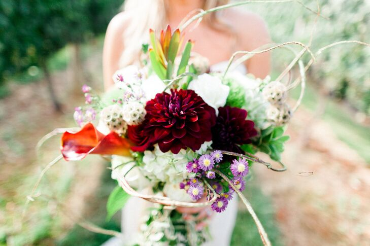 The bride's mom and sister made her bouquet the day before the wedding and incorporated various flowers from their garden. The rustic blooms included lilies, roses, hydrangeas, golden rod, ivy and magnolia leaves.
