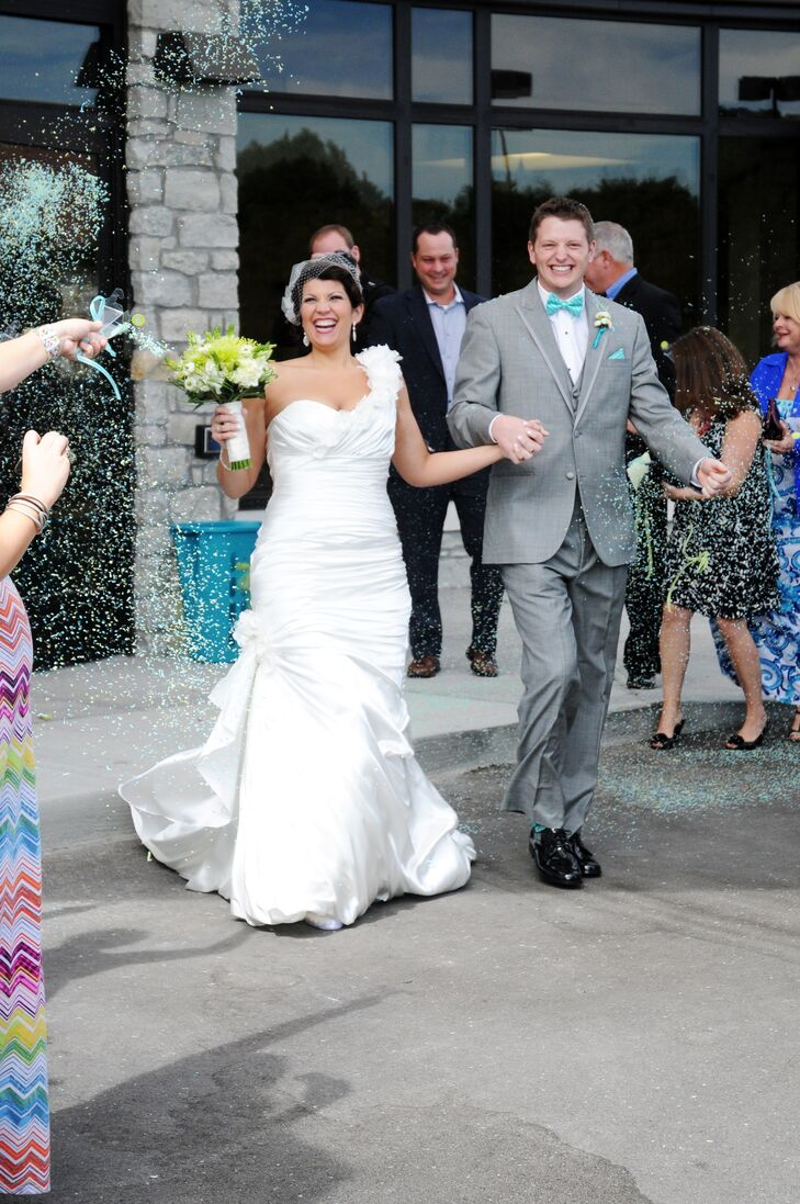 The guests tossed theme-hued turquoise and lime green confetti as the bride and groom exited the church ceremony location.