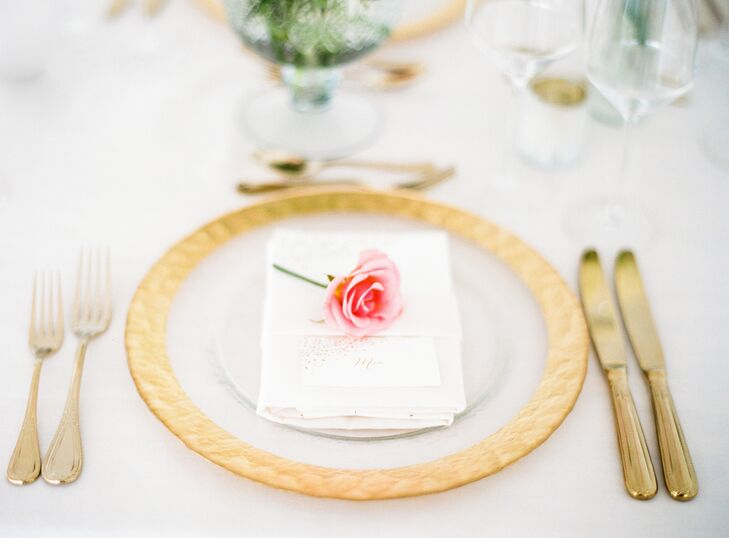 Gold-rimmed dinnerware and brass cutlery radiated in the candlelight, casting a warm, ambient glow over the sleek, modern loft space. A single pink rose was placed on each plate, helping bring the couple's romantic vision to life.