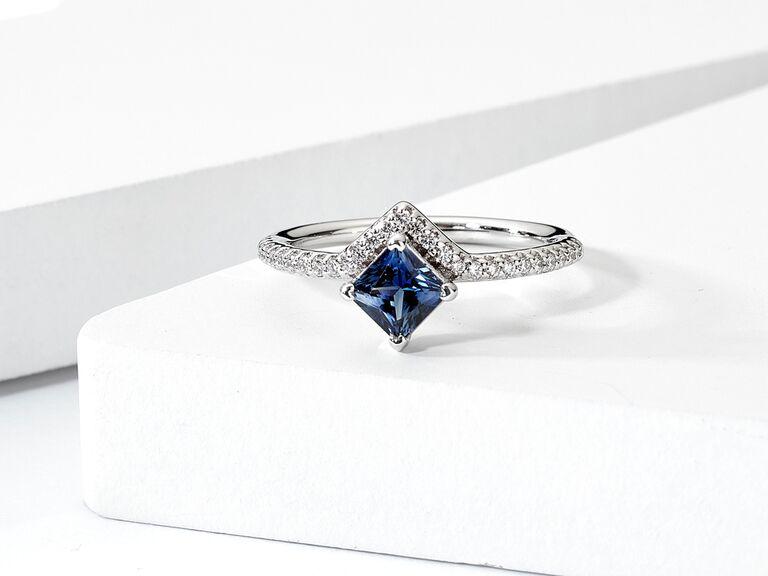 Princess cut sapphire engagement ring on diamond encrusted band