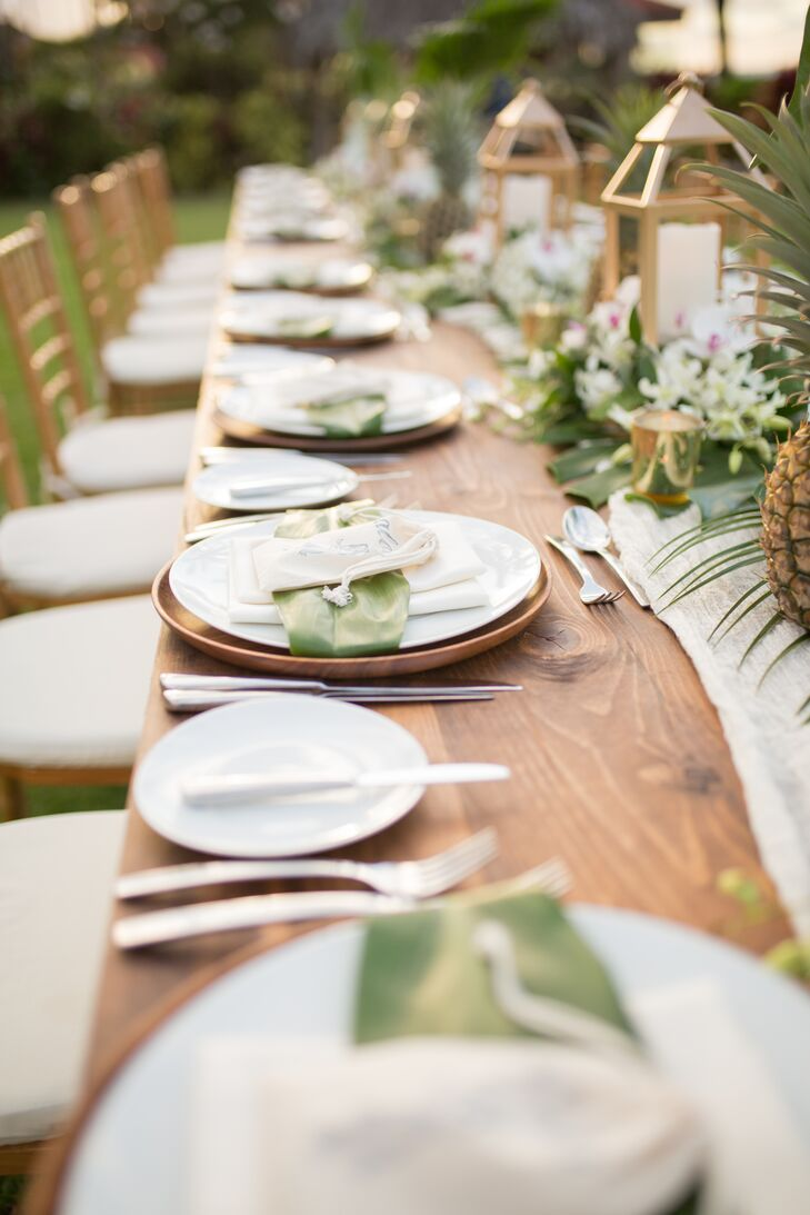 At the reception at the Four Seasons Resort Maui in Wailea, Hawaii, a long wooden banquet table was topped with simple white plates as well as fern fronds, lanterns and pineapples.