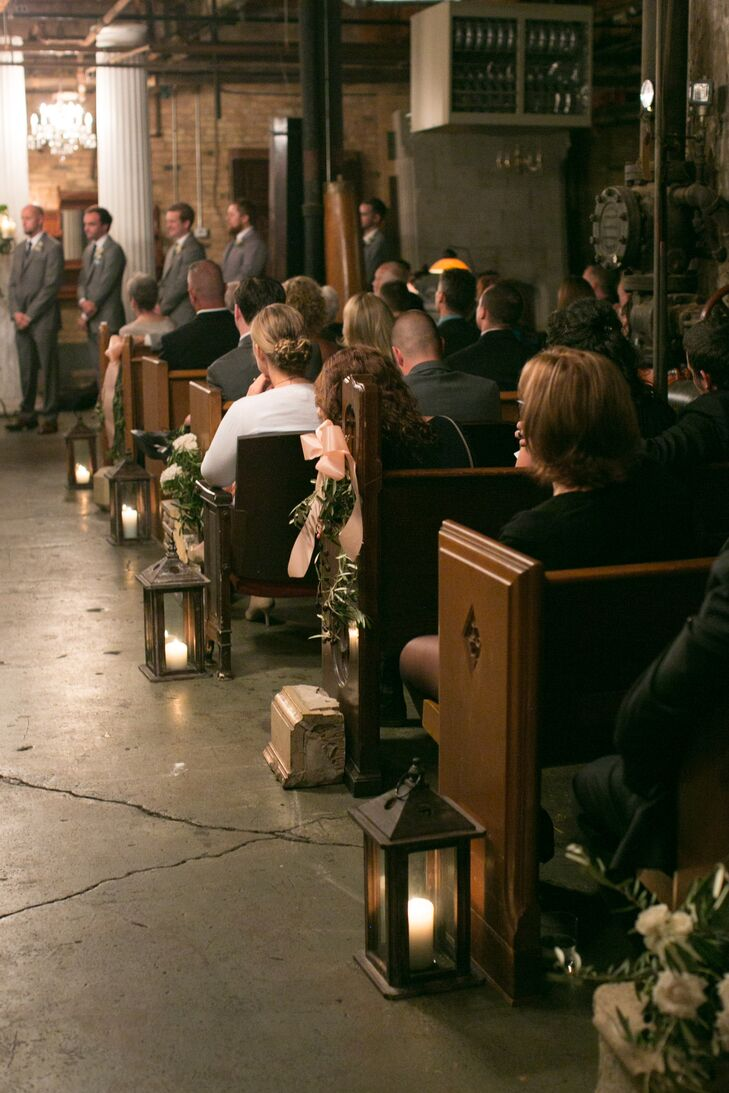 To set a romantic tone for the indoor ceremony, carriage lanterns filled with ivory pillar candles lined the aisle, casting a warm ambient glow over the room.