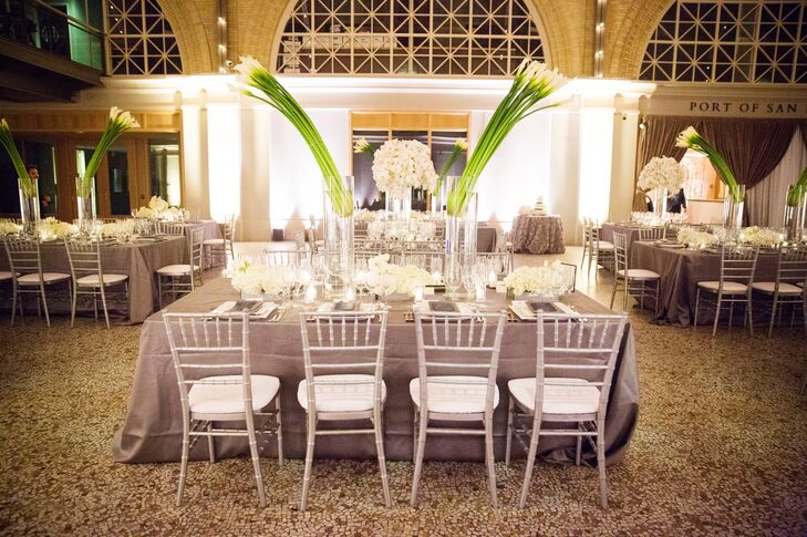 Calla lilies with long green stems stood in tall glass vases, decorating the middle of dining tables dressed in gray linens with silver chiavari chairs. These arrangements also decorated the aisle during the ceremony, and went with the rest of the white flowers seen throughout the wedding day.