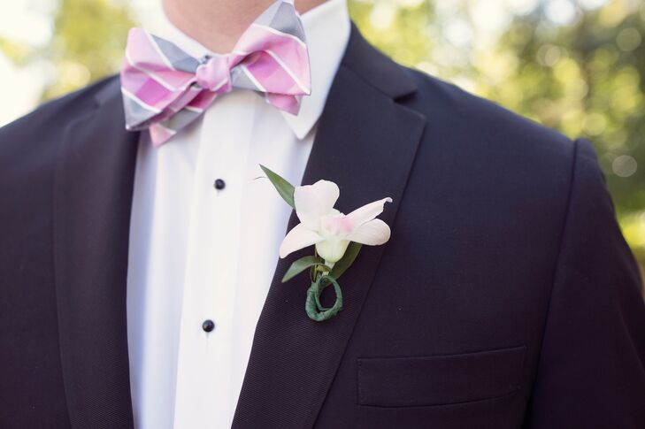 The groom wore a classic black tuxedo that he accessorized with a blush boutonniere and a black bow tie for the ceremony. For the reception, he changed into a whimsical pink and gray striped bow tie to match the color palette.