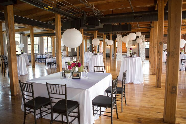 Large white paper lanterns hung above simple white tables surrounded by black Chiavari chairs for the modern reception decor.
