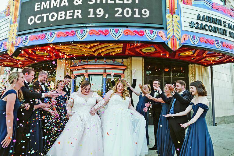 Two brides exiting retro movie theater amid cascade of confetti
