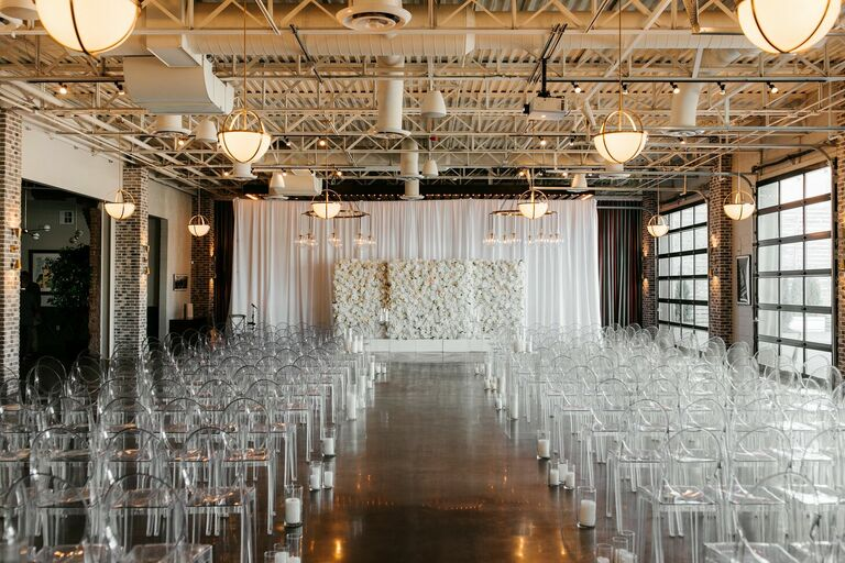 Loft wedding ceremony with ghost chairs and white flower wall