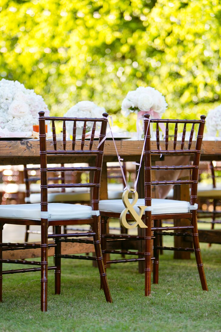 The couple's reception seating stood out with one simple and chic accent. A gold ampersand hung from pink ribbon between their two chiavari chairs.