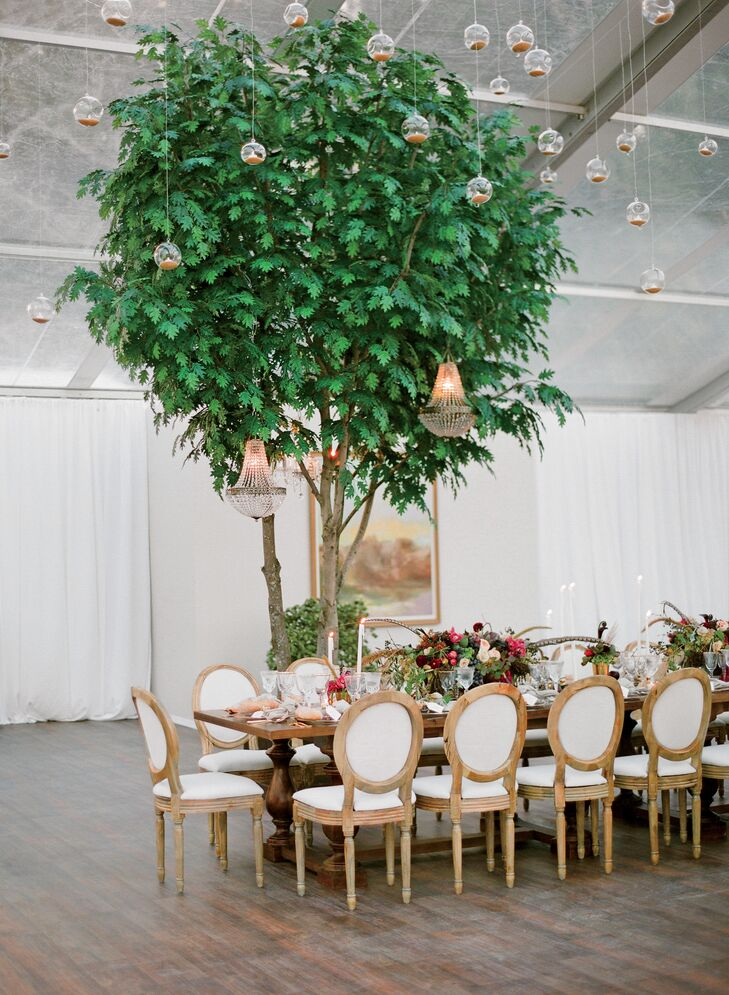 A thousand candles hung from the ceiling and decorated the tented reception along with lush trees, exposed wood tables and whimsical floral centerpieces with feather accents.