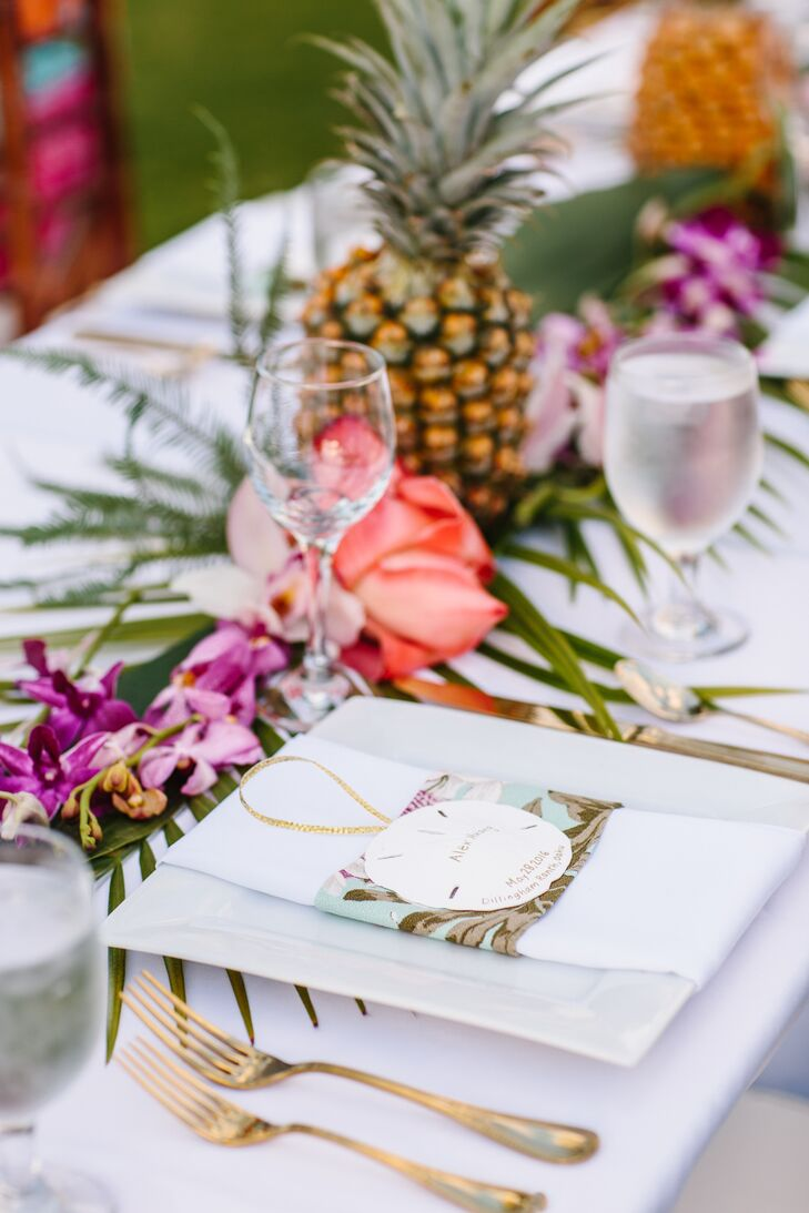 For centerpieces, Olivia and Clayton lined tables with pineapples, then scattered Hawaiian flowers down the length of each table at Dillingham Ranch in Waialua, Hawaii.