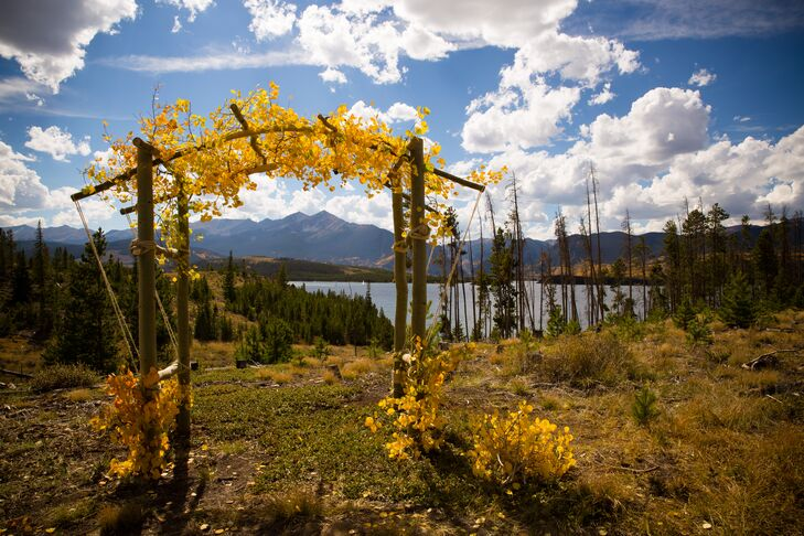 """The campground offered wonderful views across the reservoir and towards the Ten Mile Range,"" Sarah says. The couple exchanged vows under a rustic wooden arbor adorned with yellow flowers and leaves."