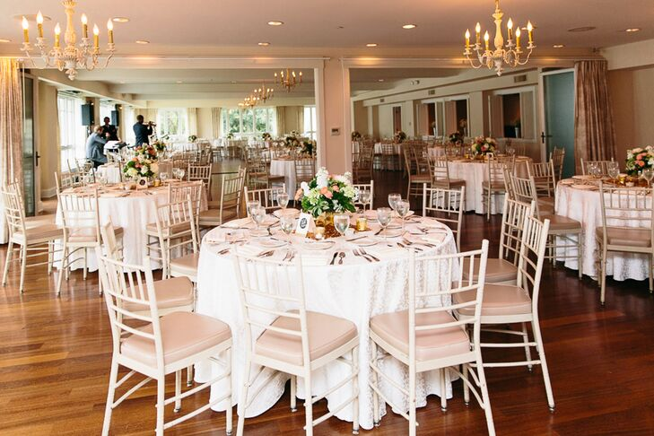 The reception was held in the ballroom at Oaks Waterfront Inn, which featured gold chandeliers that perfectly matched the wedding's color palette. Round dining tables were simply set with white linens and arranged with pink cushioned white chiavari chairs.