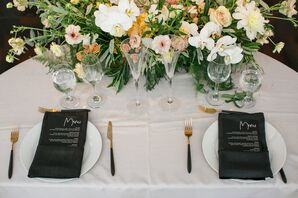 Elegant Place Setting with Black Menus and Gold Flatware