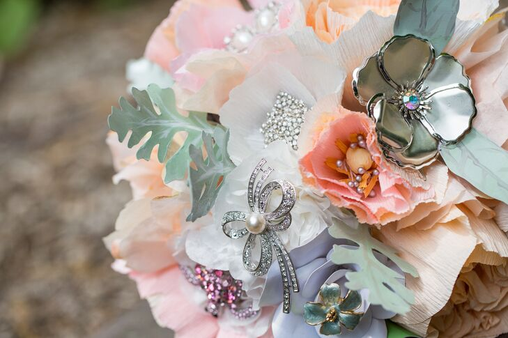 """Instead of a traditional bouquet with live flowers, Lindsey wanted something that could last beyond the wedding day. Each bridal shower guest was asked to bring a brooch to be used in the bouquet. Handmade flower vendor Regular Frills crafted a full bouquet entirely out of paper, adorned with the brooches. """"I wanted to hold what looked like a real bouquet of flowers—sweet, romantic, soft, luscious, real flowers that wouldn't die—and carry shiny little sentiments of support from my loved ones,"""" Lindsey says."""