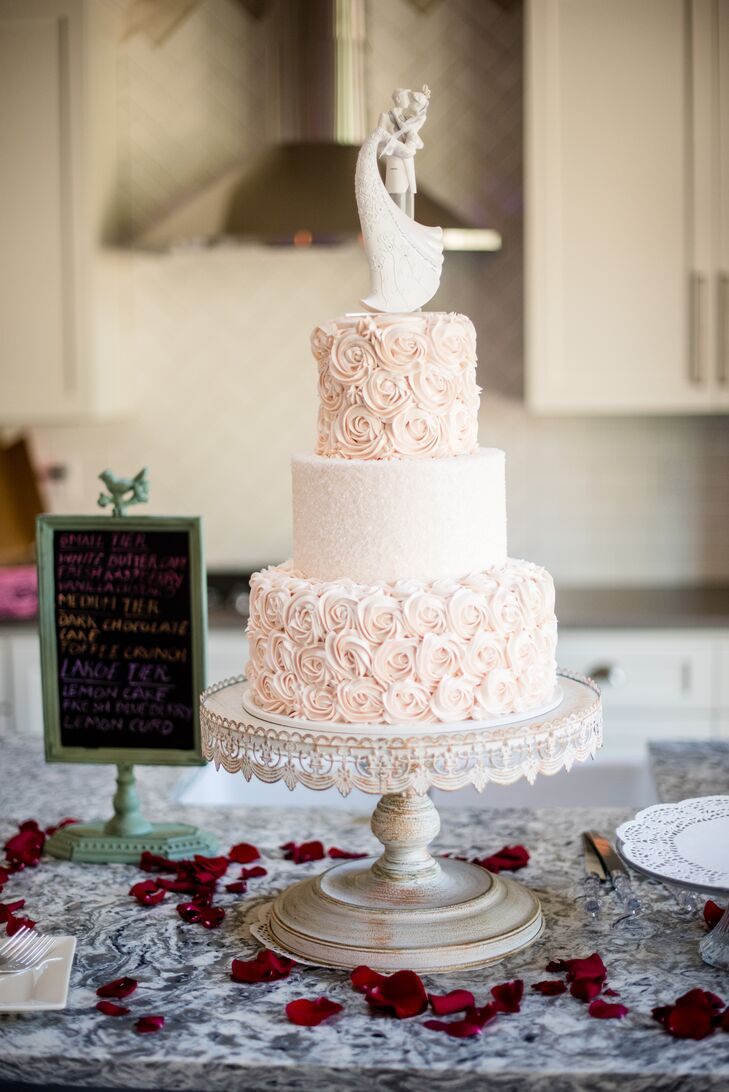 Dream Cakes bakery created a three-tier cake decorated with exquisitely detailed pale pink rosettes.