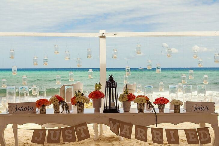 """Senor"" and ""Senora"" signs marked Marta and Jose Luis's beachfront sweetheart table, lined with coral and white potted blooms. Hanging votives enhanced the romance of the beach backdrop."