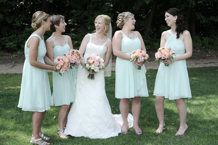 The maid of honor and bridesmaids stood next to Amy in mint green cocktail dresses from David's Bridal. With varying necklines, each bridesmaid sported light gray open-toe sandals and heels. Amy's maid of honor accessorized her outfit with a statement necklace while the bridesmaids wore drop earrings.