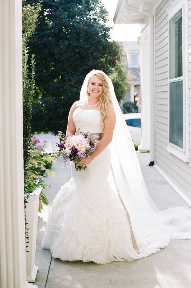 Ashley's Maggie Sottero gown perfectly captured the whimsical feel of the wedding's garden locale. The mermaid-style dress featured draped detailing along the bodice, leading to a full skirt with textured rosette detailing. She added a lavender ribbon to highlight her waist and tie the look into the day's romantic purple and pink color palette.