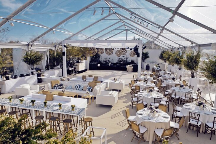 By covering the pool with a clear Navi-Trac tent, the couple was able to use the house's sun deck as a balcony overlooking the dance floor. Towering arrangements of Russian olive trees lined the perimeter of the tent. Geometric wood lamps and sheer linen panels hung above the dance floor, drawing guests eyes upwards.