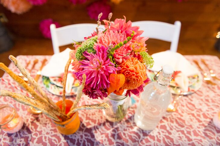 The sweetheart table stood out from the rest of the guests' tables with a darker hued tablecloth covered in a lace overlay. Placed on top of the table was a textured, bright centerpiece of mums and dahlias in pink and orange.