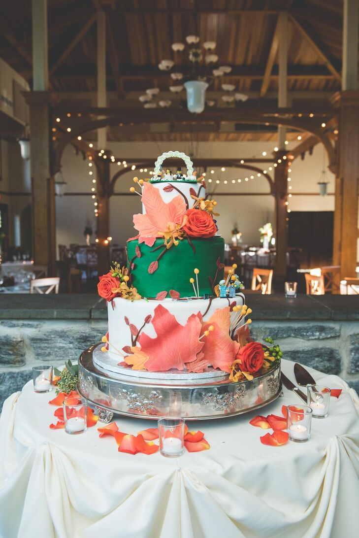 The three-tier pumpkin-spice wedding cake featured autumn leaves falling from the top with a green middle tier. Lego characters throughout the cake's tiers showcased shared moments in the couple's lives.