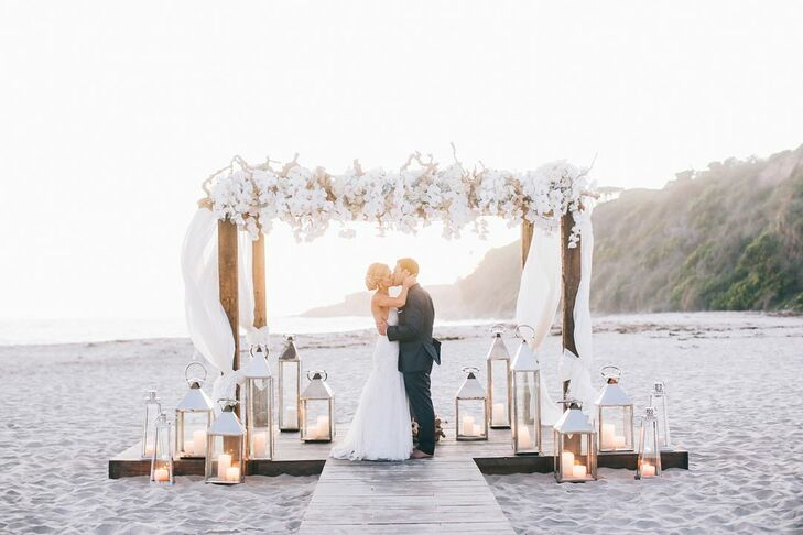 Leah and Brian exchanged vows on the sand under a four-post arch made by BloomBox Designs. It was topped with white blossoms and surrounded by silver lanterns.