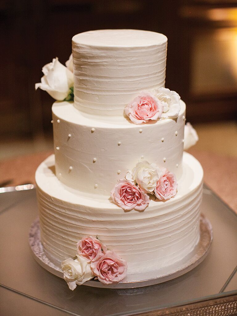 Simple white buttercream wedding cake with pink and white flowers