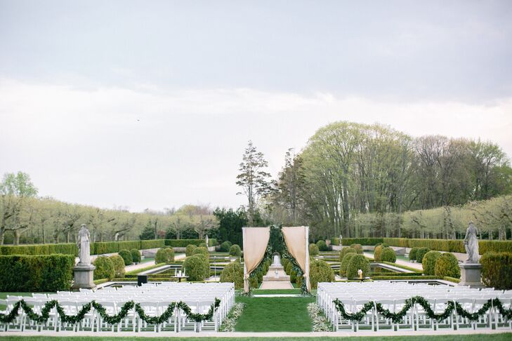 To enhance the beauty of the French Gardens at Oheka Castle—and not overpower it—Tara and Adam relied on organic shades for their ceremony decor.  One of the first things guests saw when they arrived at the outdoor ceremony were the garlands of fresh greenery draped across the last aisle of chairs.