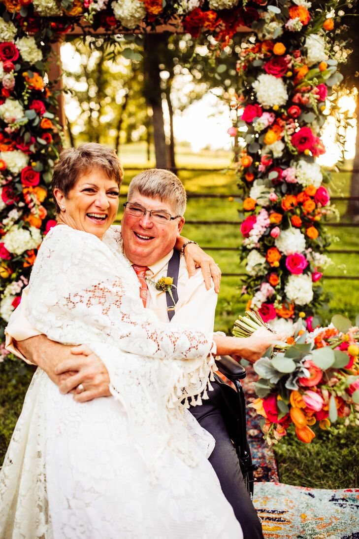 Bohemian Couple with Vibrant Flower Arch in Backyard