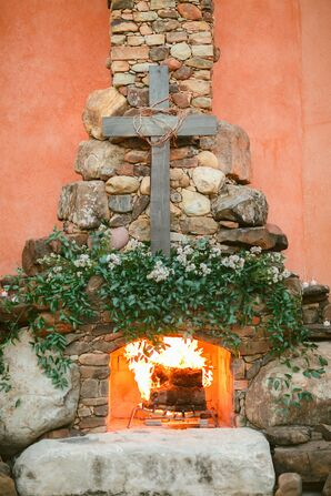 Rustic Cross on Stone Fireplace at Ceremony Venue