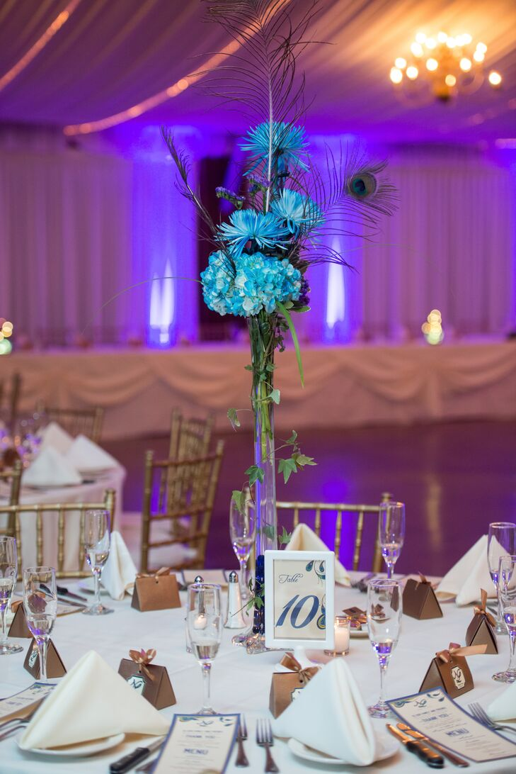 Despite the theme, Nicole wanted to minimize the use of peacock feathers in the décor to focus on the natural beauty of the venue. The feathers modestly accented the tall Eiffel tower centerpieces with blue mums.